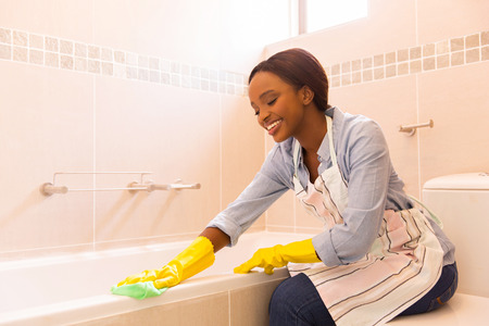 beautiful young african woman cleaning bathtub with a cloth