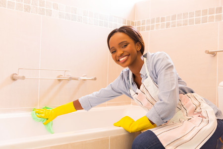 household chores: happy african girl cleaning up bathtub at home