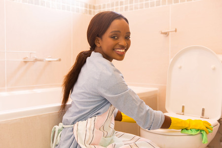 a toilet seat: pretty african girl cleaning toilet