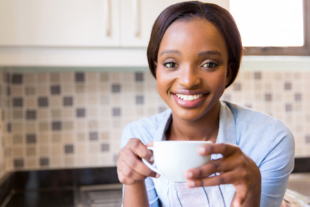 woman apron: portrait of pretty african girl drinking coffee