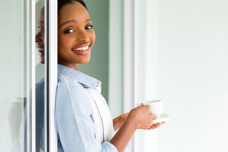 house chores: beautiful young african woman drinking tea at home after house chores