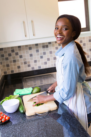 cheerful black woman cooking diner in kitchen