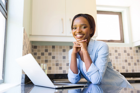 happy black woman: attractive young afro american woman using laptop in kitchen Stock Photo