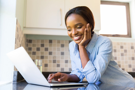 happy african woman: happy young african woman using laptop at home Stock Photo