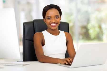 executive women: attractive african office worker using laptop computer
