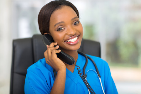 attractive african medical doctor talking on telephone photo