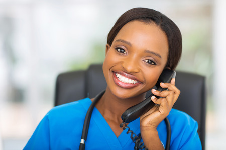 portrait of pretty african american female nurse using landline phone photo