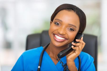 person on phone: portrait of pretty african american female nurse using landline phone