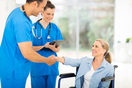 friendly middle aged medical doctor handshaking with patient on wheelchair photo