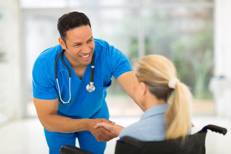 male nurse: friendly healthcare worker handshaking handicapped woman