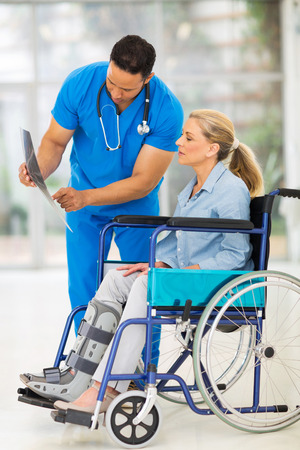 injured woman: doctor explaining x-ray results to patient in wheelchair Stock Photo