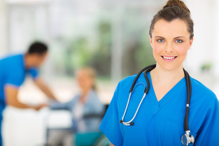 beautiful young nurse with stethoscope in doctors office photo