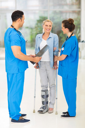 healthcare workers: friendly healthcare workers with injured woman on crutches in hospital