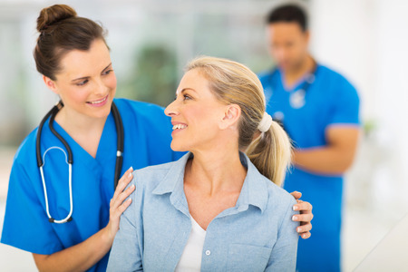 professional woman: caring nurse talking to senior woman in hospital Stock Photo