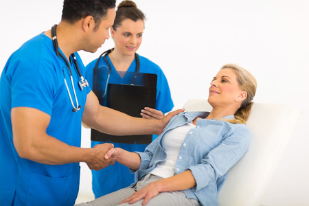 work checkup: caring male doctor greeting senior patient before medical checkup