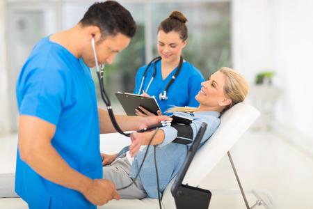 hipertension: médico que cuida que toma la presión arterial mediados de mujer de la edad Foto de archivo