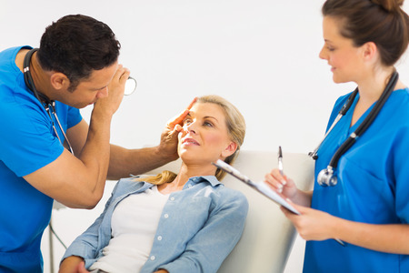 modern doctor: friendly ophthalmologist examining womans eye