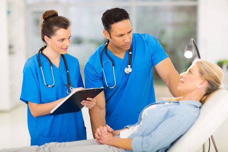 work checkup: caring health workers talking to middle aged patient before checkup Stock Photo