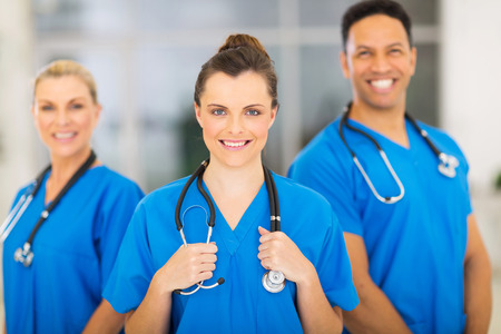 people standing: attractive medical nurse and colleagues in hospital Stock Photo