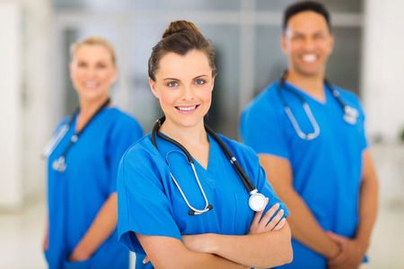 beautiful young female nurse with colleagues on background photo