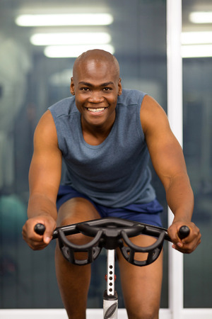 Fitness Men Working Out With Stationary Bike In Gym Stock Photo