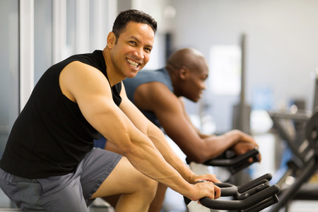 workout gym: two men doing indoor biking in a fitness club Stock Photo