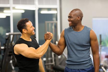 handshaking: friendly men handshaking in gym