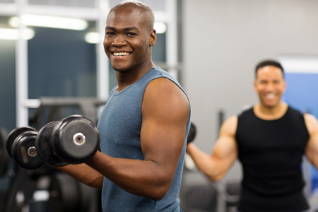 gyms: healthy african man working out with dumbbells in gym Stock Photo