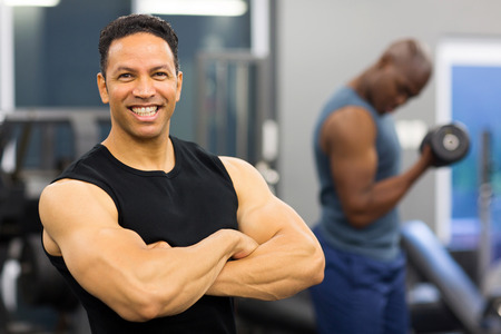 muscular man with arms crossed in gym photo