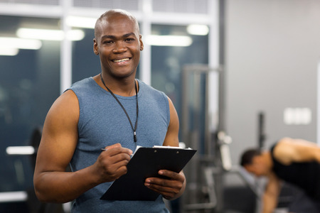 sports coach: young african american male personal trainer holding clipboard in gym