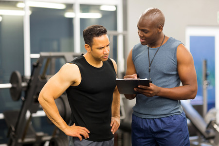 personal trainer: african personal trainer helping man to fill the membership form of health club Stock Photo