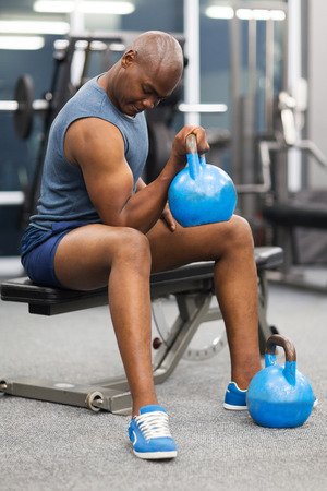 man working out: sportive african man lifting kettle bell in gym Stock Photo