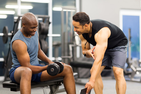 sport training: middle aged personal trainer training client in gym