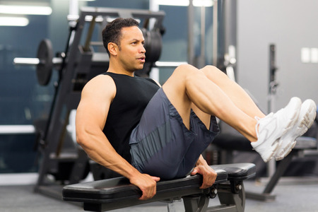 man working out: muscular hombre trabaja en el gimnasio