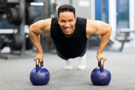 pushup: healthy man doing pushup exercise with kettle bell in gym