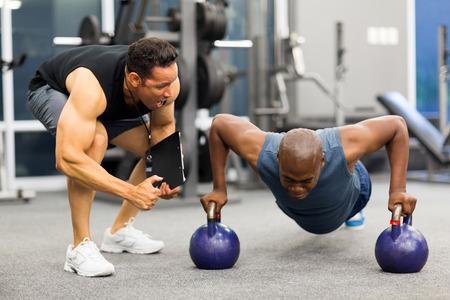 hombre deportista: entrenador personal motiva cliente haciendo flexiones en el gimnasio Foto de archivo