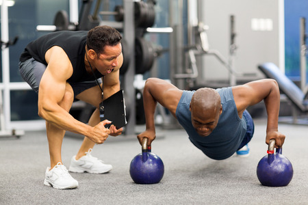 coach sport: personal trainer motivates client doing push-ups in gym Stock Photo