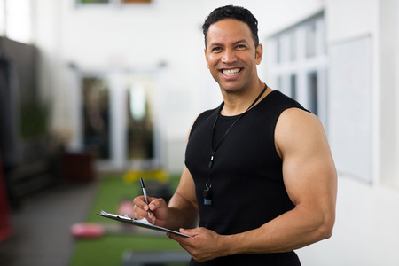 portrait of handsome mid age trainer holding clipboard photo