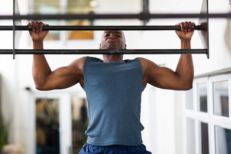 pull up: strong african man doing pull-ups on a bar in a gym
