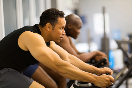 fitness men working out with stationary bike in gym