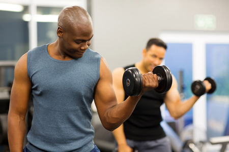fit african american athlete lifting weights in gym