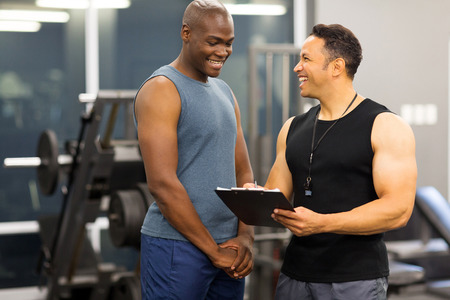 instructor explaining membership form to client in health club Stock Photo
