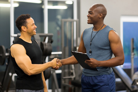 friendly african gym trainer handshaking with mid age client in gym