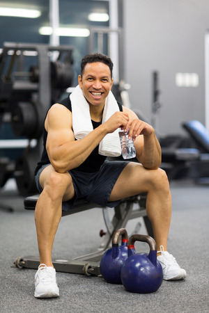 mid age: happy mid age man sitting on bench after exercise Stock Photo