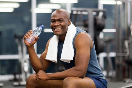tomando agua: feliz joven africano agua potable despu�s del ejercicio
