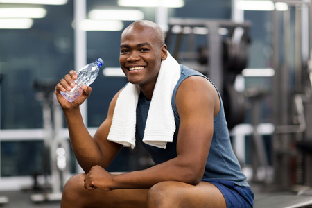 out of water: happy young african man drinking water after exercise