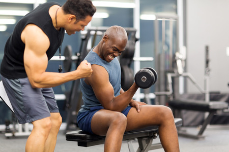 weight lifting: professional gym trainer motivating client to lift dumbbell Stock Photo