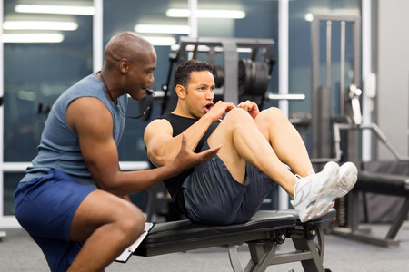 personal trainer: fit middle aged man with personal trainer in gym