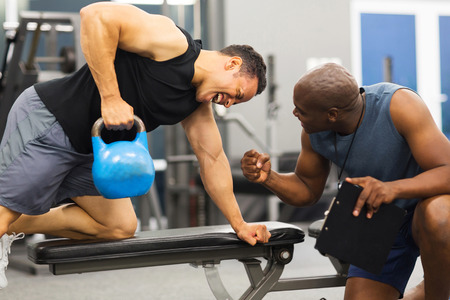 atleta: hombre entrenamiento entrenador personal con la campana hervidor de agua pesada Foto de archivo