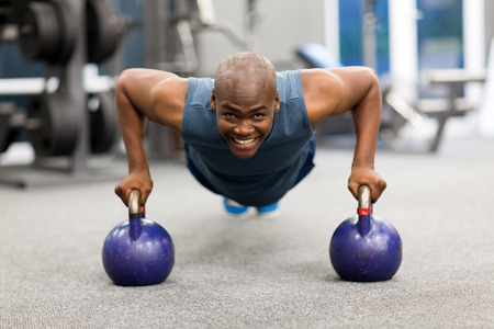 pushups: happy young african man doing push-ups exercise with kettle bells